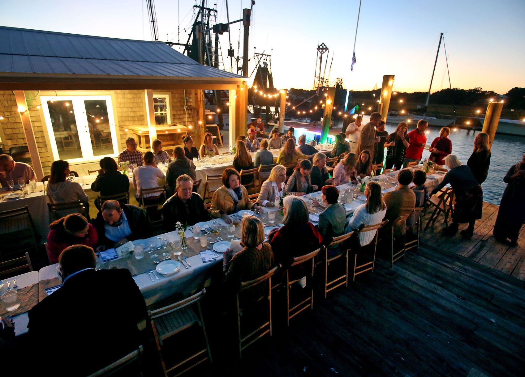 Commune Supper Club held an event at the Geechie Seafood dock on Shem Creek in Mount Pleasant featuring fish caught by Mark Marhefka and the meal created by Chefs Michelle Weaver and Lauren Mitterer. Image via postandcourier.com: Grace Beahm/Staff